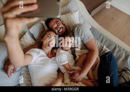 Happy young woman sticking out her tongue and taking selfie with her crazy family. Family lying on bed with funny - Stock Photo