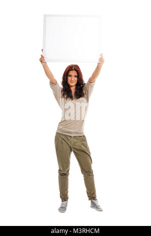 Beautiful business lady with casual wear holding white blank billboard - Stock Photo
