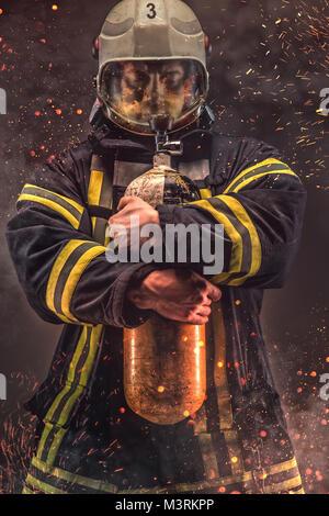 Firefighter in helmet and mask holds oxygen tanks.  - Stock Photo