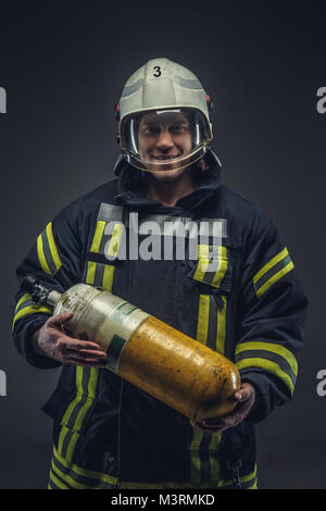 Firefighter rescue holds yellow oxygen tank.  - Stock Photo