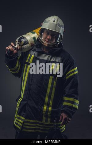 Firefighter in helmet holds oxygen tank. - Stock Photo