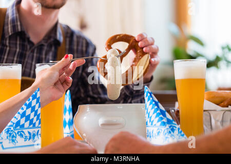 People eating veal sausage in bavarian restaurant - Stock Photo