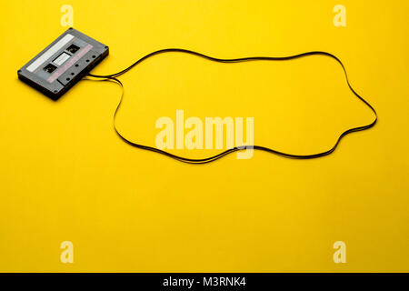 Retro cassette tape over yellow background. top view. copy space - Stock Photo