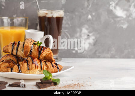 Fresh breakfast of croissants with chocolate syrup, orange juice and cocoa with marshmelow. - Stock Photo