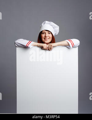 Picture of smiling brunette chef in white dressing-gown cap with empty paper in hands - Stock Photo