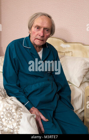 Elderly man getting into bed - Stock Photo