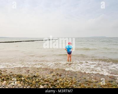 Boy in blue black sporty clothes stay in cold foamy sea. Blond hair  kid in  waves at stony beach.  Windy day, cloudy - Stock Photo