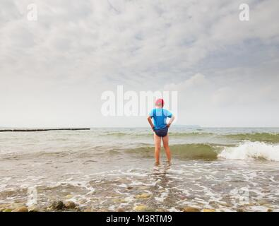 Children on the beach go into the ocean. Kid play in the waves of foamy sea. - Stock Photo
