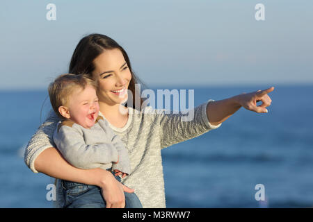 Happy mother and kid laughing and pointing horizon on the beach in a sunny day - Stock Photo