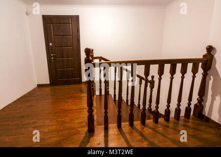 Close-up detail of brown wooden oak stairs in new renovated house. Staircase between two floors - Stock Photo