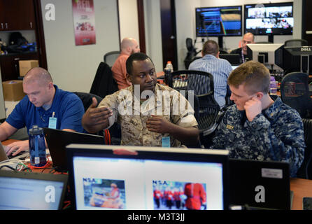 Marine Gunnery Sgt. Dadrian Mills (center) conducts Cyber Defense Exercise Red Cell operations with fellow team - Stock Photo