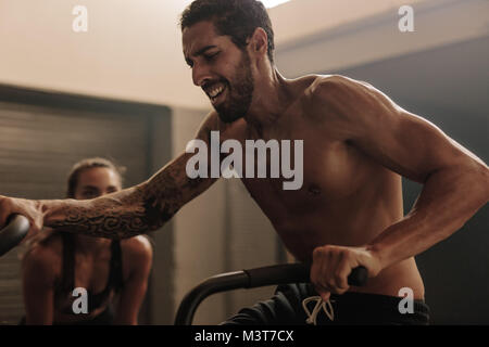 Man on bicycle doing spinning at gym with trainer. Fit young male working out on gym bike with female coach. - Stock Photo