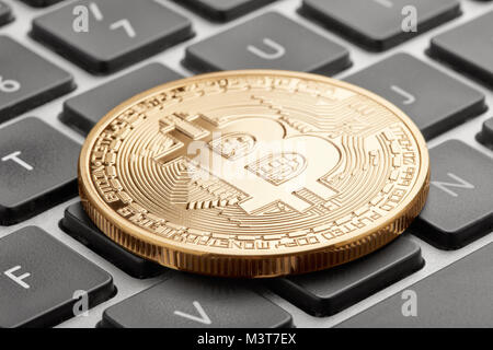 Golden bitcoin on computer keyboard with black keys - Stock Photo