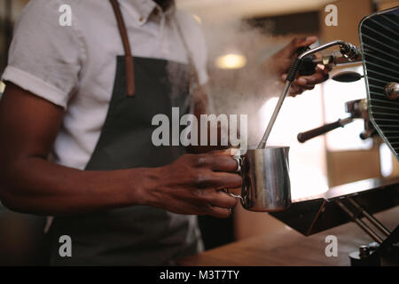 Coffee shop owner preparing coffee on steam espresso coffee machine. Cropped shot of man working in his coffee shop - Stock Photo