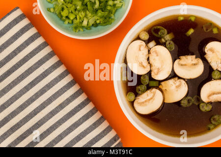 Bowl Of Japanese Style Clear Onion Soup With Mushrooms and Spring Onions - Stock Photo