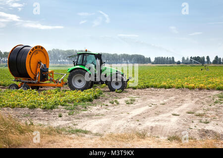 agriculture irrigation machine on a farm field during a long period without rain - Stock Photo