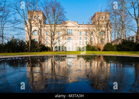 Reichstag parliament building reflected in pond at Memorial to the Sinti and Roma of Europe Murdered Under national - Stock Photo