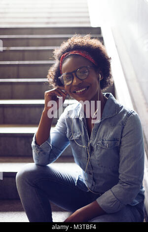 Stylishly dressed young African woman smiling while sitting alone at the bottom of a stairwell listening to music - Stock Photo