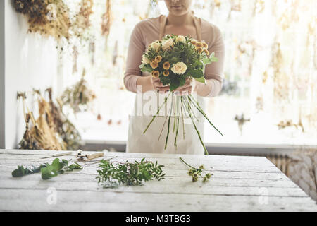 Closeup of a female florist standing at a table in her flower workshop holding a bouquet of roses and mixed flowers - Stock Photo
