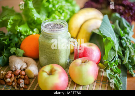 A glass of green smoothie surrounded by fresh fruit and green leafy vegetables. - Stock Photo