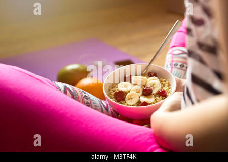 Young girl eating a oatmeal with berries after a workout . Fitness and healthy lifestyle concept. - Stock Photo
