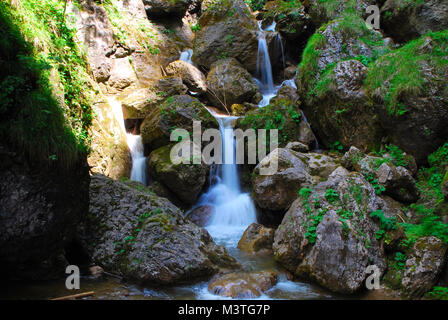 beautiful clear waterfall in between many large rock mountain - Stock Photo