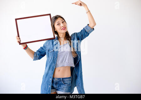 Body language concept - smiling young playful woman showing an empty right shoulder side display of a product for - Stock Photo