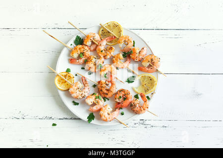 Grilled shrimp skewers. Seafood, shelfish. Shrimps Prawns skewers with spices and fresh herbs on white wooden background, - Stock Photo