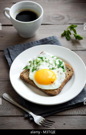 Fried Egg on Toast and cup of Coffee for Breakfast. Fried egg with bread on plate over wooden table, top view, copy - Stock Photo