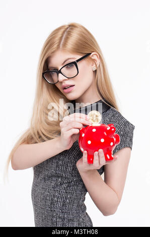 Young smart blonde woman put bitcoin into piggy bank, isolated on white - Stock Photo
