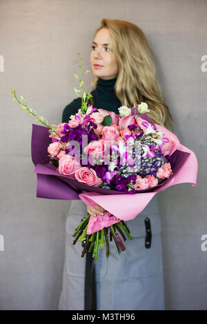 The beautiful rustic bouquet in purple tones in woman hands on grey background - Stock Photo