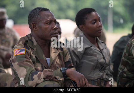 A Gabonese Armed Forces Soldier, wearing an American Flag patch, listens tentatively to an instructor from the Defense - Stock Photo