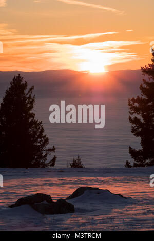 View from some rocks on mountain Schoeckl through trees to low stratus over city Graz to mountain Koralpe and sunset - Stock Photo