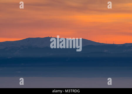 View from mountain Schoeckl over low stratus to mountain Koralpe with pinwheels and sunset - Stock Photo