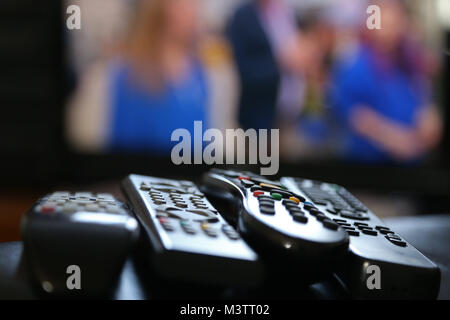 A range of remote controls for television, satellite, DVD and sound system, on the arm of a chair, in Peterborough, - Stock Photo
