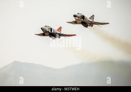 Two McDonnell Douglas F-4 Phantom IIs of the 82nd Aerial Target Squadron Detachment 1 steak over the flightline - Stock Photo