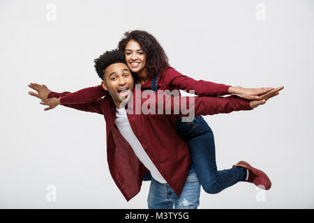 Close-up young african american couple riding back and playing like plane. - Stock Photo