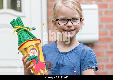 A blond girl in glasses looks forward to his first day at school and poses with the school bag on her doorstep. - Stock Photo