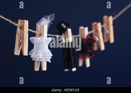 Bride and groom clothespin toys, clothesline. Abstract woman in white dress and man character with black suit hat. - Stock Photo