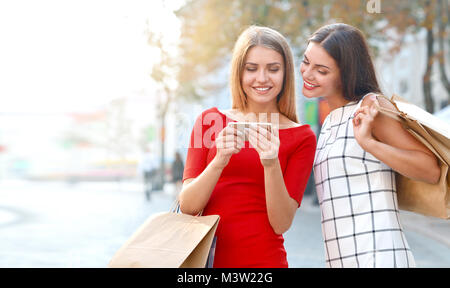 Woman shows on a mobile phone something to his girlfriend. Happy young women with smartphone on city street - Stock Photo