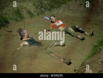 Army Sgt. James Nickelson (left) and Patterson share a laugh as they lie in a mud pit during a mud bogging competition. - Stock Photo