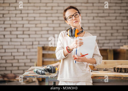 hardworking professional female worker with pen and tablet in workshop - Stock Photo