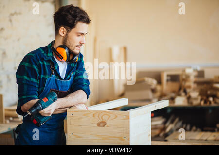 Young male carpenter in workshop looking at camera - Stock Photo