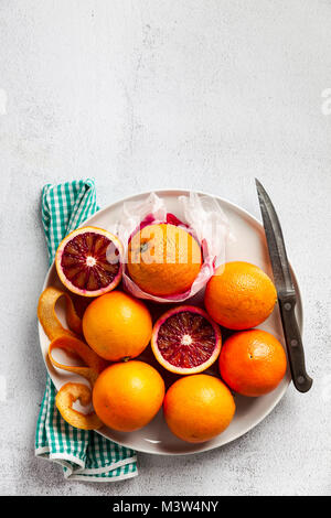 A group of oranges on a plate. some of them cut. knife and towel. on a stone background. a healthy summer table, - Stock Photo