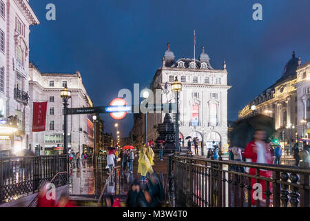 People with umbrellas, Piccadilly circus, rain, evening, Subway entrance, London, UK - Stock Photo