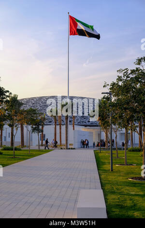 United Arab Emirates Flag waving high in front of Louvre Museum Abu Dhabi - Stock Photo