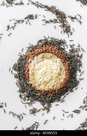Different kinds of rice on the white background - Stock Photo