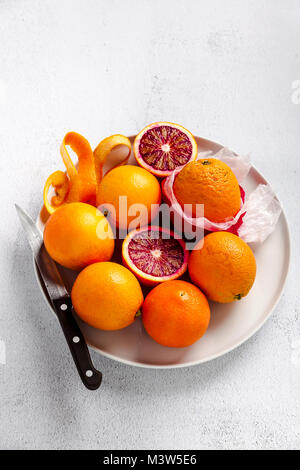 A group of oranges on a plate. some of them cut. knife . on a stone background. a healthy summer table, the preparation - Stock Photo