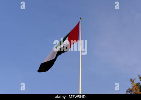 United Arab Emirates Flag waving high in the wind with isolated sky in background - Stock Photo