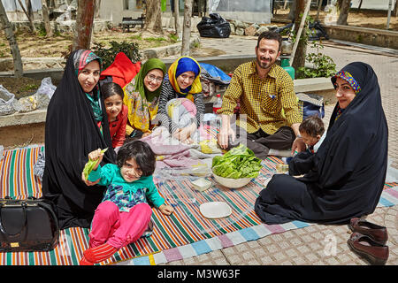 Tehran, Iran - April 28, 2017: big Iranian family is spending a day off making a picnic in the park, they are smiling - Stock Photo